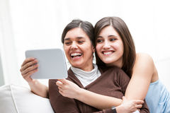 Мать и дочь смеясь над по мере того как они принимают selfie Стоковые Фотографии RF