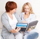 Мать и дочь смотря книгу фото Стоковые Фотографии RF
