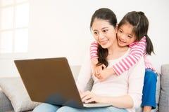 Мать и дочь смотря компьтер-книжку Стоковая Фотография