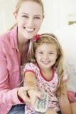 Мать и дочь смотря ТВ совместно стоковая фотография