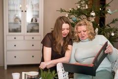 Мать и дочь смотря фотоальбом Стоковые Изображения RF
