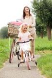 Мать и дочь с велосипедами в парке Стоковая Фотография