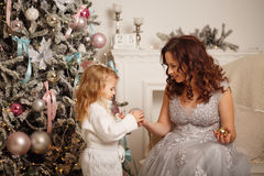 Мать и дочь украшают рождественскую елку Стоковые Фото