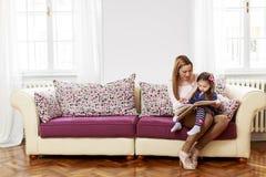 Мать и дочь читая совместно Стоковое Изображение RF