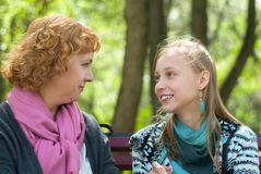 Мать и предназначенная для подростков дочь на скамейке в парке стоковая фотография rf