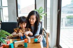 Мать и ребенк играя с деревянным блоком стоковое фото