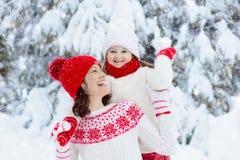 Мать и ребенок в связанных шляпах зимы в снеге стоковая фотография