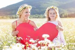 Мать и ребенок держат красное бумажное сердце Стоковые Изображения RF
