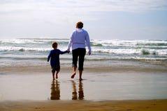 Мать и ребенок держа руки идя на пляж стоковые изображения