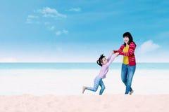 Мать и ребенок играя на пляже Стоковая Фотография