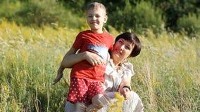Мать и ребенок идут на поле лета, счастливы и смеяться над акции видеоматериалы