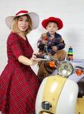 Мать и ребенок нося старомодные одежды представляя близко scoot Стоковое Фото