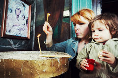 Мать и ребенок освещая свечи в церков Стоковая Фотография RF