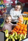 Мать и ребенок покупая мандарины в рынке Стоковые Изображения RF