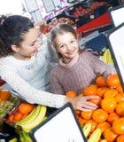 Мать и ребенок покупая мандарины Стоковые Фото