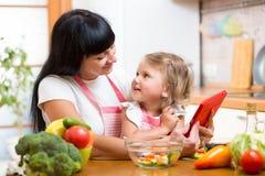 Мать и ребенок подготавливая овощи совместно на кухне и lo Стоковое Изображение RF