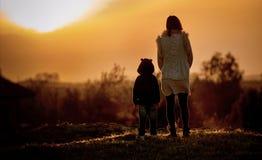 Мать и ребенок смотря заход солнца Стоковая Фотография RF