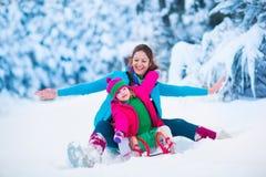 Мать и ребенок sledding в снежном парке Стоковые Изображения RF