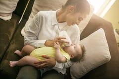 Мать и ребёнок дома Мать подавая ее маленькое Стоковые Фотографии RF