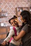 Мать и счастливая дочь обнимая один другого Стоковые Изображения