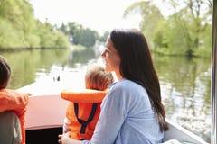 Мать и сыновьья наслаждаясь днем вне в шлюпке на реке совместно стоковое изображение rf