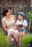 Мать и сынок имея ослабляют на тросточк-стуле outdoors стоковое фото rf
