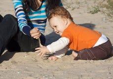Мать и сынок сидя на пляже Стоковая Фотография RF