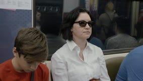 Мать и сын едут поезд на метро, в вечере Сын хочет спать, его мерцание глаз видеоматериал