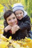 Мать и сын лежа на листьях осени Стоковые Фото