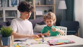 Мать и сын занятые создающ красочный бумажный коллаж сидя на таблице дома акции видеоматериалы