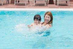 Мать и сын играя в бассейне Стоковые Изображения RF