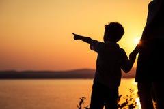 Мать и сын играя на пляже на времени захода солнца стоковая фотография rf