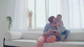 Мать и сын играя с цифровым планшетом дома Молодая мать с ее 5 летами старый усмехаться с цифровым планшетом на сток-видео