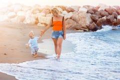 Мать и сын идя на пляж захода солнца стоковое изображение rf