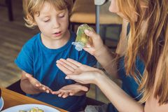 Мать и сын используя мытье вручают гель дезинфицирующего средства в кафе стоковое изображение rf