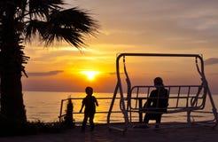 Мать и сын и красивый заход солнца над морем Стоковое фото RF