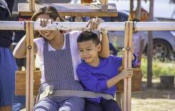 Мать и сын на деревянном колесе Ferris и ярком голубом небе на kho Windtime Khao, Phetchabun в Таиланде стоковое изображение rf