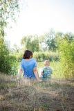 Мать и сын на речном береге стоковое изображение