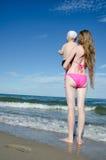 Мать и сын на руках на береге моря смотря в расстояние Стоковое Изображение