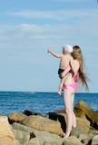 Мать и сын на руках среди камней на береге моря смотря в расстояние Стоковая Фотография RF
