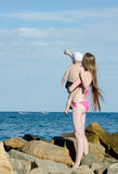 Мать и сын на руках среди камней на береге моря смотря в расстояние Стоковые Фотографии RF