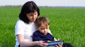 Мать и сын ослабляют в парке сидя на зеленой траве Семья использует планшет для игры, для того чтобы смотреть фильма, или делает сток-видео
