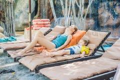Мать и сын ослабляя на loungers солнца бассейном Стоковое Изображение