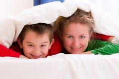 Мать и сын под одеялом усмехаясь жизнерадостно стоковое изображение rf