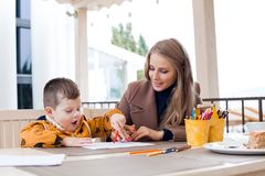Мать и сын рисуют карандаши чертежа покрашенные руками Стоковая Фотография RF