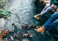 Мать и сын сидят на деревянном мосте над потоком горы Стоковые Изображения