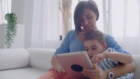 Мать и сын сидя на софе используя цифровой планшет Счастливые мама и мальчик используя планшет с сенсорным экраном совместно сток-видео