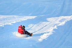 Мать и сын сползая на трубопровод снега вниз с холма стоковые фото