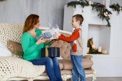 Мать и сын с подарками на рождество перед мех-деревом с свечами Стоковые Изображения RF
