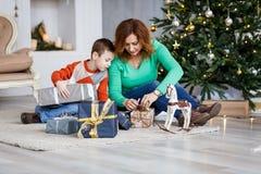 Мать и сын с подарками на рождество перед мех-деревом с свечами Стоковая Фотография RF